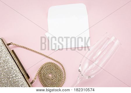 Festive Evening Golden Clutch And Champagne Glass On Pink. Holiday And Celebration Background. Luxur