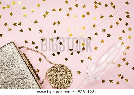 Festive Evening Golden Clutch And Champagne Glass With Star Sprinkles On Pink. Holiday And Celebrati