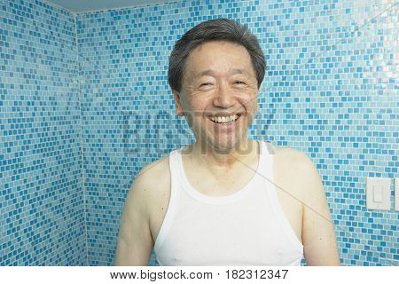 Smiling Asian man in bathroom