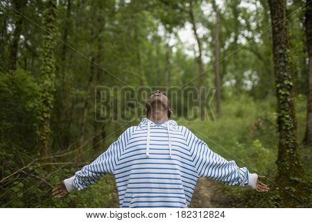 African boy in forest with arms outstretched