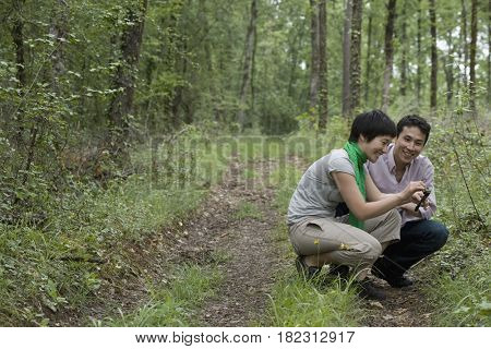 Asian couple examining nature in forest