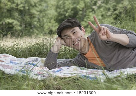 Asian man laying on blanket in park