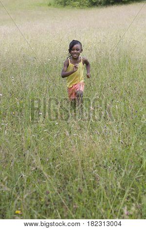 African girl running in field