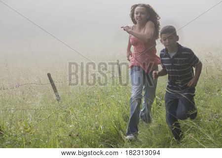 Mixed race brother and sister racing in field