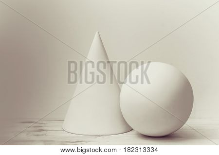 Simple geometric shapes cone and sphere. Elementary construction in art school.