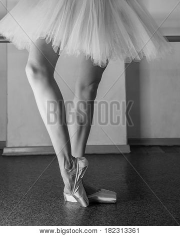 A ballerina in pointes and a pack warms up before the dance lesson. Long slender female feet. Classical ballet. Prima ballerina. Black and white photography