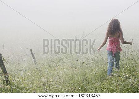 Mixed race girl walking in remote field