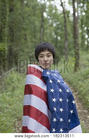 Asian woman wrapped in American flag in forest