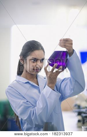 Indian scientist working in laboratory with beaker of liquid