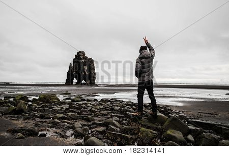 Traveler man standing on stones at Hvitserkur black sand beach, in Iceland