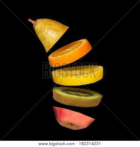 Surrealistic creative concept with flying fruit. Pieces of pear, orange, lemon, kiwi and apple on a black background