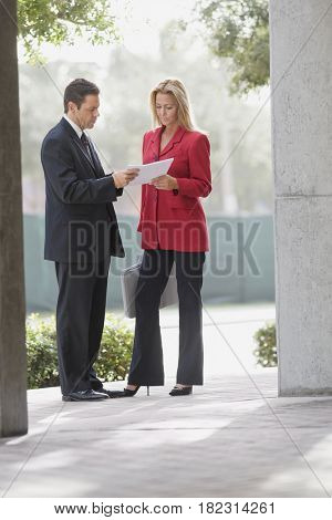 Businesspeople reviewing paperwork outdoors