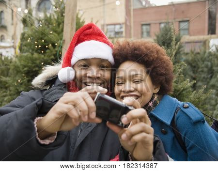 African man in santa hat taking self-portrait with girlfriend