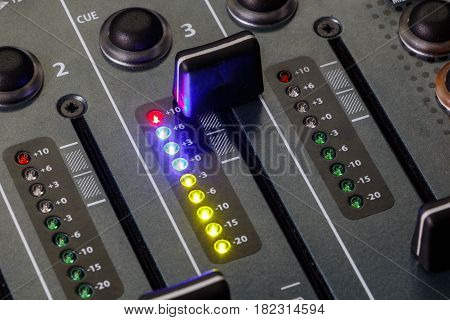 Close up shot of a DJ mixer volume faders with volume levels in the red