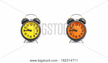 Closeup yellow alarm clock and orange alarm clock for decorate show a quarter to ten o'clock or 9:45 a.m. isolated on white background