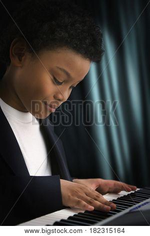 Mixed race boy playing keyboard