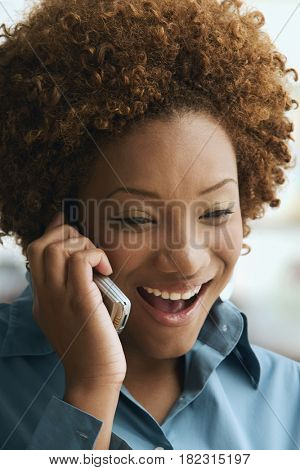 Smiling Hispanic woman talking on cell phone