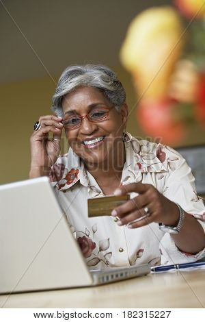 African woman ordering merchandise online with credit card
