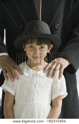 Hispanic girl standing with father wearing his hat