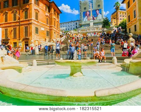 Rome, Italy - September 10, 2015: Spanish steps and Ugly Boat fountain surronded by hundreds of tourists with Trinita dei Monti church on background at Rome, Italy on September 10, 2015