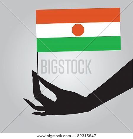 Flag of Niger in a female hand. Vector illustration.