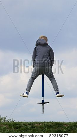 boy on Pogo Stick jumping up and down