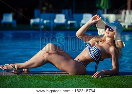 A beautiful young girl is lying on the ledge of the pool. She is wearing a pretty swimsuit, sunglasses and hat. She is sunbathing