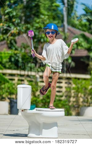 Absurd Picture: Cute Boy Dancing On The Toilet, Which Is Installed In The Middle Of The Street. Pan