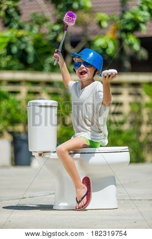 Absurd Picture - Astride A Toilet: Cute Boy In Goggles Sitting On The Toilet, Which Is Installed In