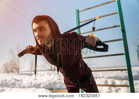 Male caucasian or middle eastern adult working out. Young fit man exercising with fitness straps. Winter workout.