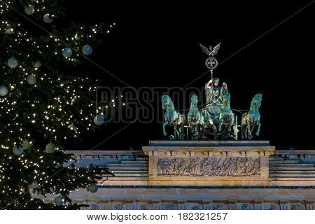 A fragment of the Brandenburg Gate (Quadriga close-up) and a fragment of a Christmas tree in the foreground.