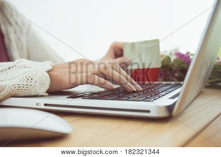 Vintage tone of Woman's hands holding a credit card and using laptop for online shopping