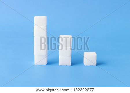 High to low stacks of sugar cubes with blue background health care concept