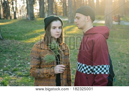 two happy homeless man and woman hold pine stick in the evening