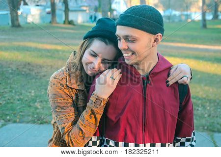two happy homeless man and woman stick together