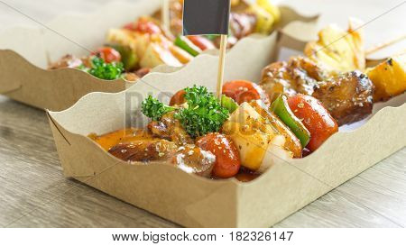 Barbecue or BBQ party food concept - Close up chicken barbecue or BBQ in paper tray with flag on wood floor and copy spcae