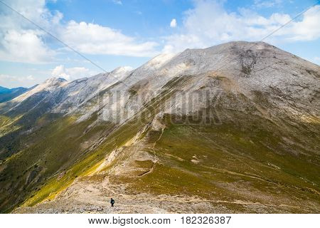 View from under the peak Vihren to the marble part of Pirin mountain Bulgaria. Hiker in distance alone on long curvy highland trail over steep mountain range.