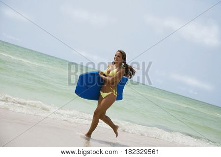 Mixed race woman carrying boogie board at beach