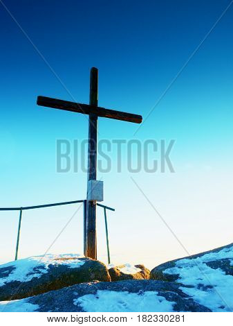 Modest Wooden Cross On Rocky Summit. Memory Of Victims
