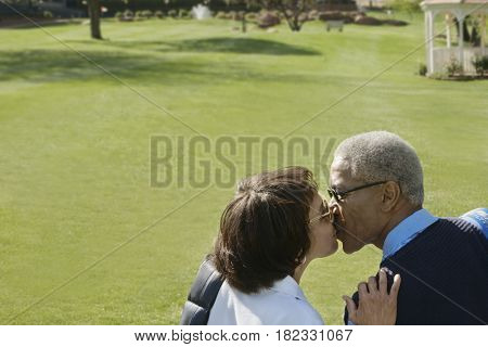 African couple kissing on golf course