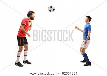 Full length profile shot of a son and a father dressed in jerseys playing with a football isolated on white background