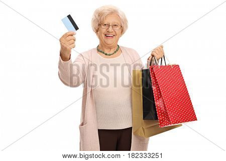 Cheerful elderly woman with a credit card and shopping bags isolated on white background