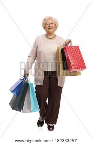 Full length portrait of a joyful mature woman with shopping bags walking towards the camera isolated on white background