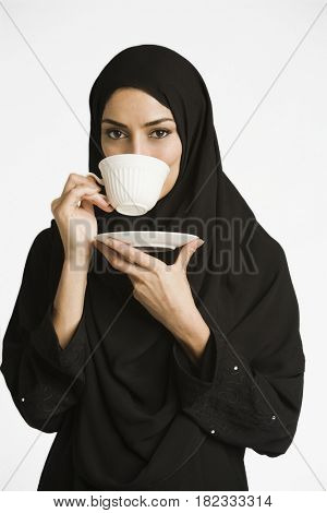 Middle Eastern woman in burkha drinking coffee