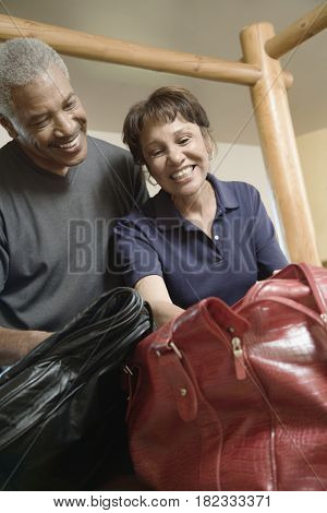 African couple packing suitcases