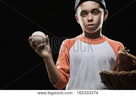 Mixed race boy holding baseball and baseball glove