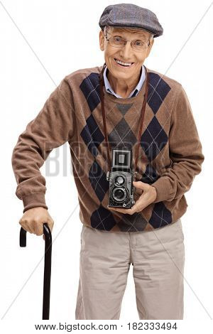 Happy senior with a vintage camera and a walking cane looking at the camera isolated on white background