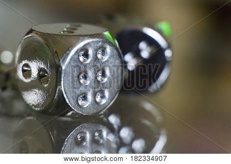 Two metal dices on glass background. Macro shot.