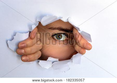 the green-eyed girl looking through torn paper. spying glancing