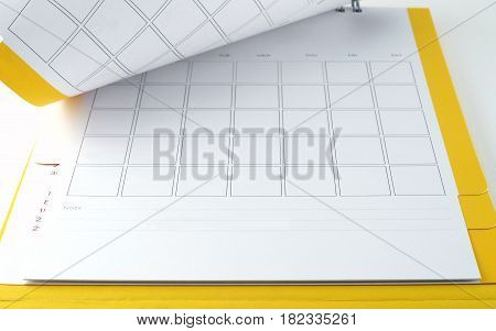 blank yellow desk calendar with lines for notes on white background, flip the calendar page